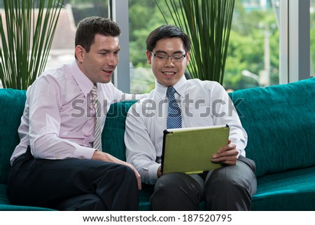 Two businesspeople watching something on the screen of the digital tablet - stock photo