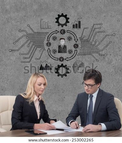 two businesspeople working in office and drawing business scheme on wall - stock photo