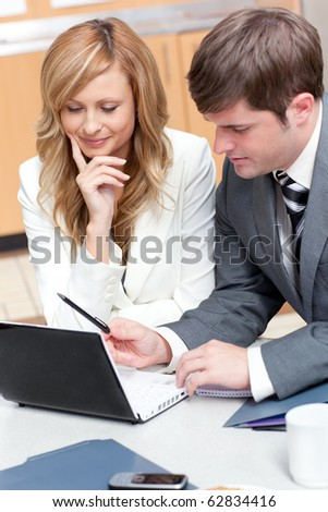 Two businesspeople working on a presentation in their office