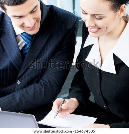 Two businesspeople working with document at office - stock photo