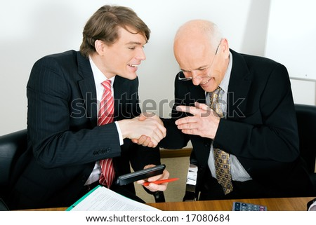 Two Businesspeople (younger and a senior figure) shaking hands agreeing on a deal looking really happy - stock photo