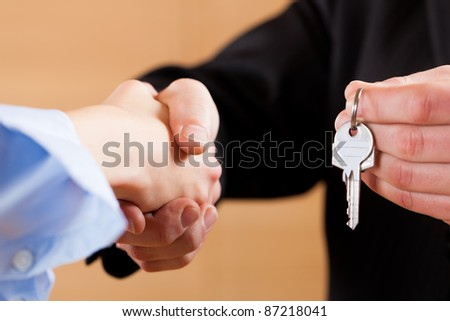 Two businessperson shaking hands; only hands to be seen and a key is be given - stock photo
