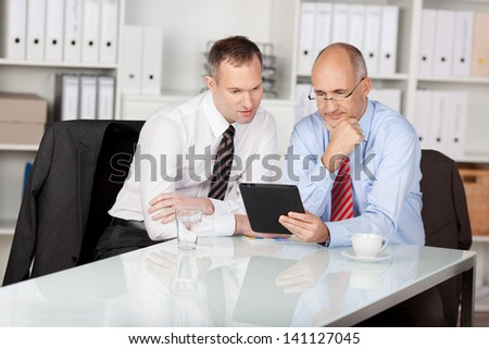 Two businesspersons looking at the tablet computer inside the office - stock photo