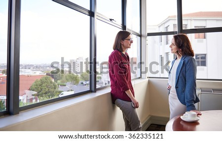 Two businesswoman colleagues standing in a corner office with views of buildings and the city through large windows, engaged in a positive discussion - stock photo