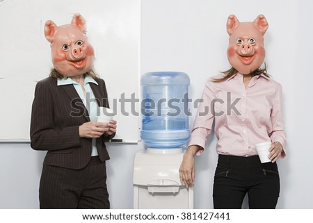 Two businesswoman in pig masks at a water cooler - stock photo