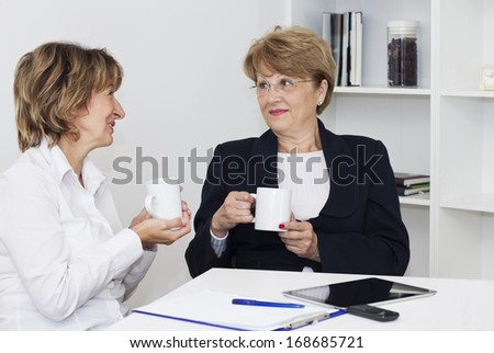 Two businesswoman sitting at the desk with cup of coffee and talking. - stock photo