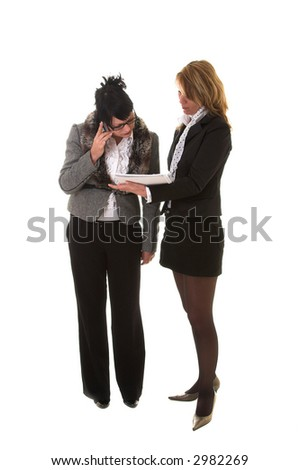 Two businesswoman standing; one on the phone and the other holding a notebook out to her