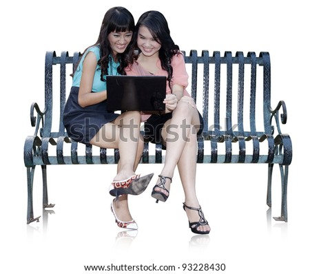 Two businesswoman working with laptop on white background - stock photo