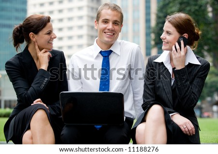 Two businesswomen and a businessman outside with laptop and phone