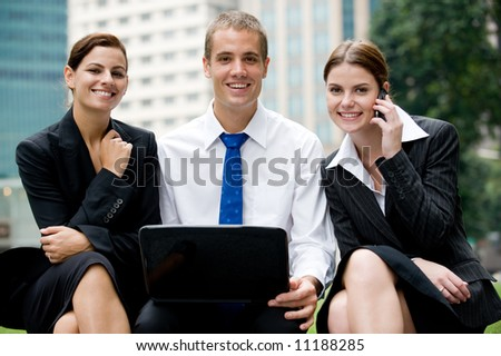 Two businesswomen and a businessman outside with laptop and phone - stock photo