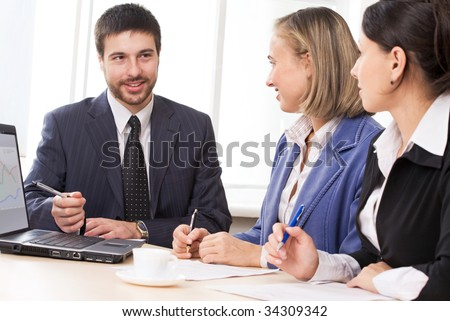 Two businesswomen and a businessman working in team on the background of a window