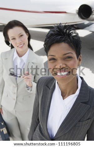 Two businesswomen at the airfield - stock photo