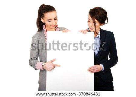 Two businesswomen carrying a big white board. - stock photo