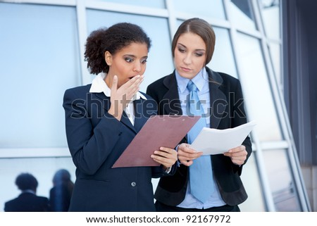 two businesswomen checking document , terrible mistake