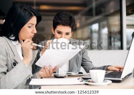 Two businesswomen consulting on meeting - stock photo