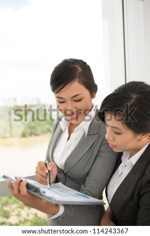 Two businesswomen discussing financial charts