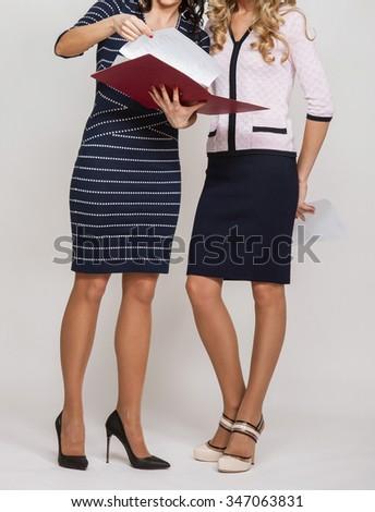 Two businesswomen examining documents, neutral background - stock photo