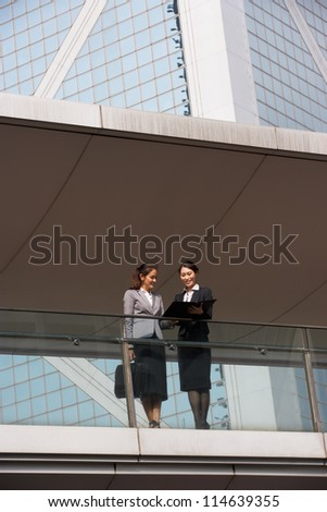 Two Businesswomen Having Discussion Outside Office Building - stock photo