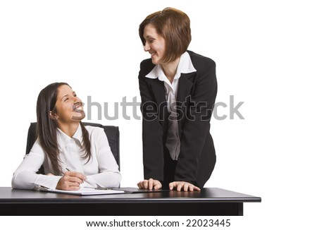 Two businesswomen having fun while they are working together.