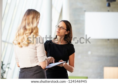 Two Businesswomen Having Informal Meeting In Modern Office - stock photo