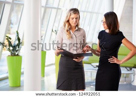 Two Businesswomen Having Informal Meeting In Modern Office - stock photo