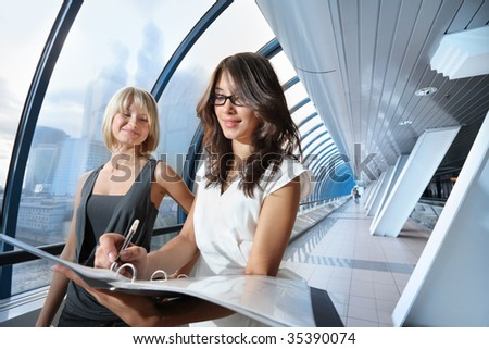 Two businesswomen looking into papers in futuristic interior - stock photo