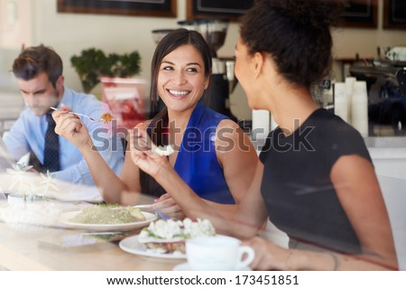 Two Businesswomen Meeting For Lunch In Coffee Shop - stock photo