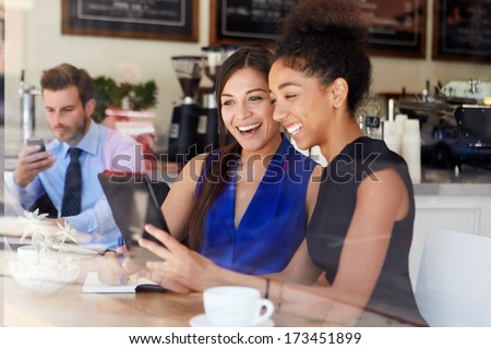 Two Businesswomen Meeting In Coffee Shop - stock photo