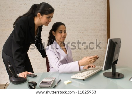 Two businesswomen reviewing items on a computer screen - stock photo