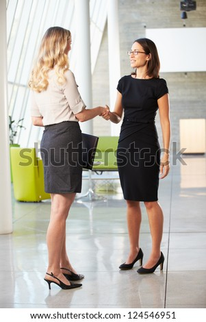 Two Businesswomen Shaking Hands In Modern Office - stock photo