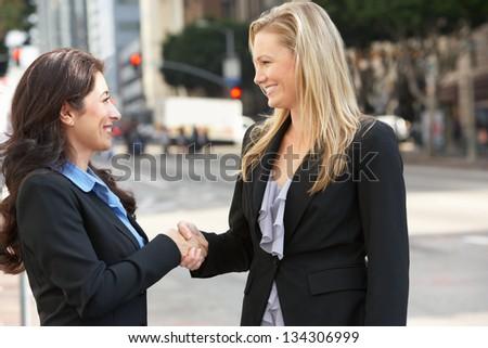 Two Businesswomen Shaking Hands Outside Office - stock photo