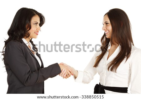 Two businesswomen shaking hands. Women smiling and looking at each other.