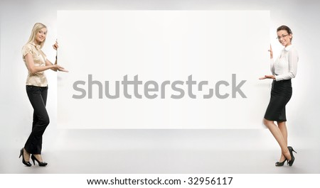 Two businesswomen showing an empty board,lots of copyspace - stock photo