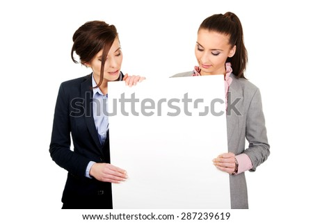 Two businesswomen showing white empty banner. - stock photo