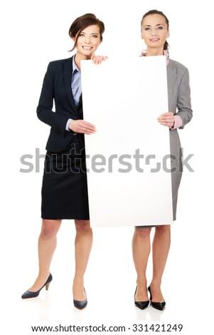 Two businesswomen showing white empty banner. - stock photo