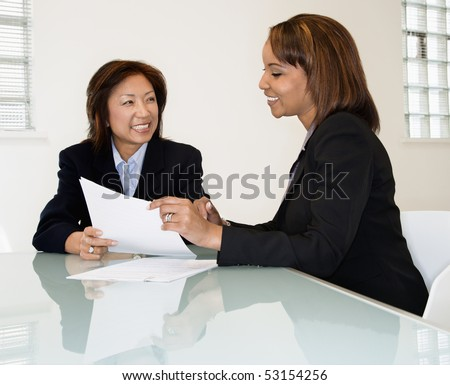 Two businesswomen sitting at office desk having meeting and discussing paperwork. - stock photo