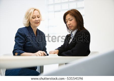 Two businesswomen sitting at office desk looking and talking over papers.