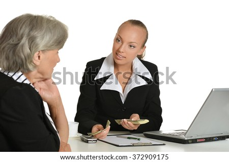 Two businesswomen sitting at table - stock photo