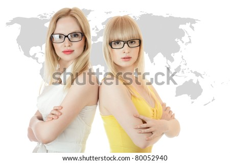 Two businesswomen standing together back to back against world map - stock photo