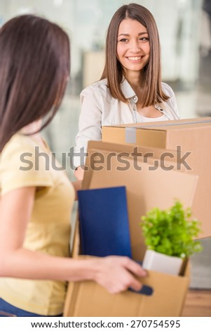 Two businesswomen surrounded by boxes in their new office. - stock photo
