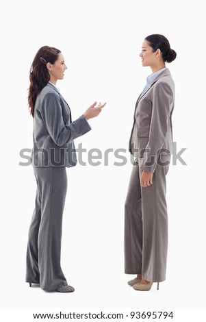 Two businesswomen talking face to face against white background - stock photo