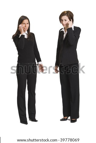 Two businesswomen using mobile phones isolated against a white background. - stock photo