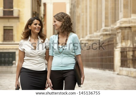 Two businesswomen walking through town together - stock photo
