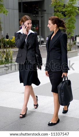 Two businesswomen walking together outside - stock photo