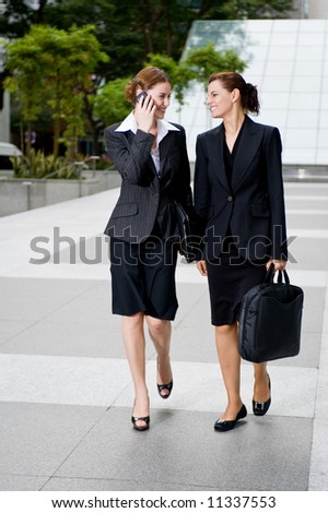 Two businesswomen walking together outside
