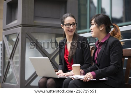 Two businesswomen with laptop in a modern urban setting. Caucasian and Asian business women. - stock photo