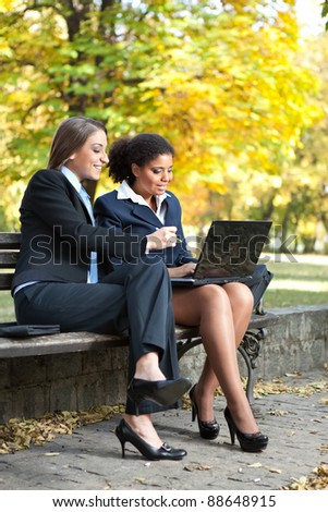 two businesswomen working on laptop in park
