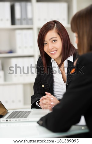 Two businesswomen working together as a team in the office sitting at a desk sharing a laptop with focus to a friendly Asian woman facing the camera with a smile - stock photo