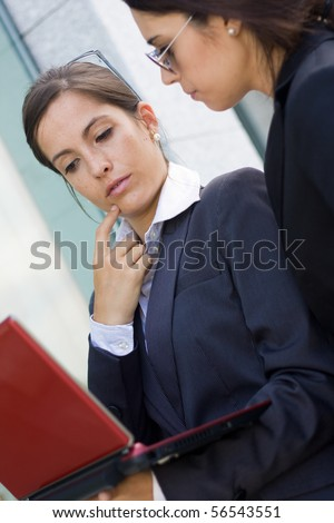 two businesswomen working with laptop - stock photo