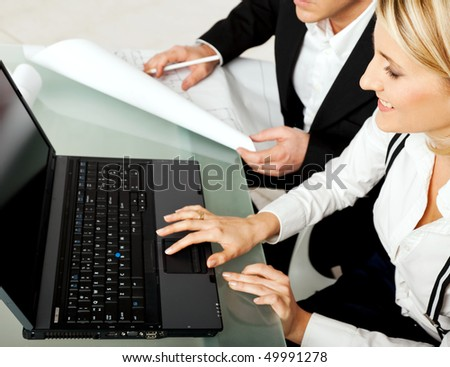 Two bussines persons, engineers, architects sitting on desk with blueprints and laptop